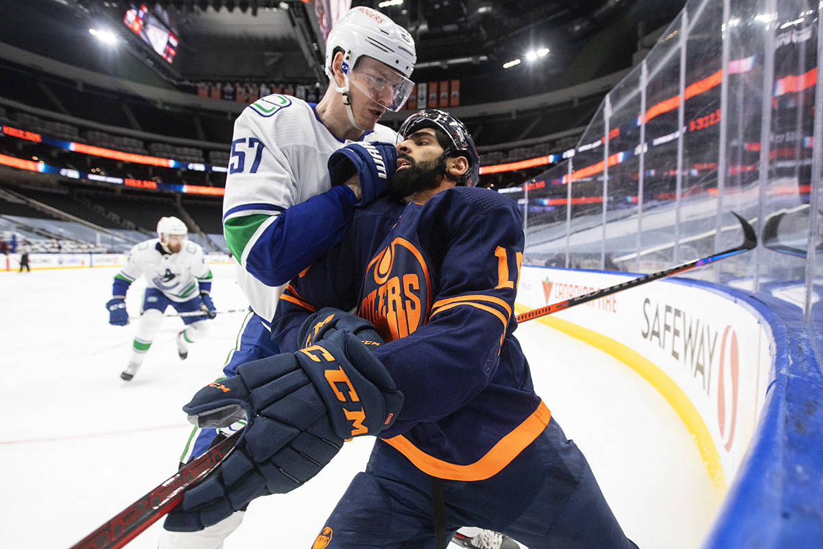 Edmonton Oilers' Jujhar Khaira (16) is checked by Vancouver Canucks' Tyler Myers (57) during second period NHL action in Edmonton on Saturday, May 15, 2021. THE CANADIAN PRESS/Jason Franson