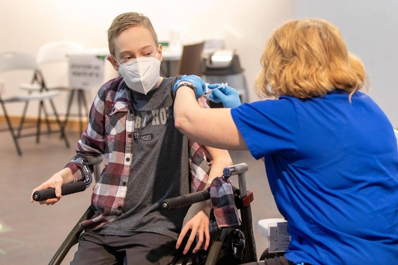 Riley Oldford, 16, suffers from cerebral palsy. He was the first youth in the Northwest Territories to get a COVID-19 vaccine. Here he receives the needle from nurse practitioner Janie Neudorf in Yellowknife on Thursday May 6, 2021. THE CANADIAN PRESS/Bill Braden