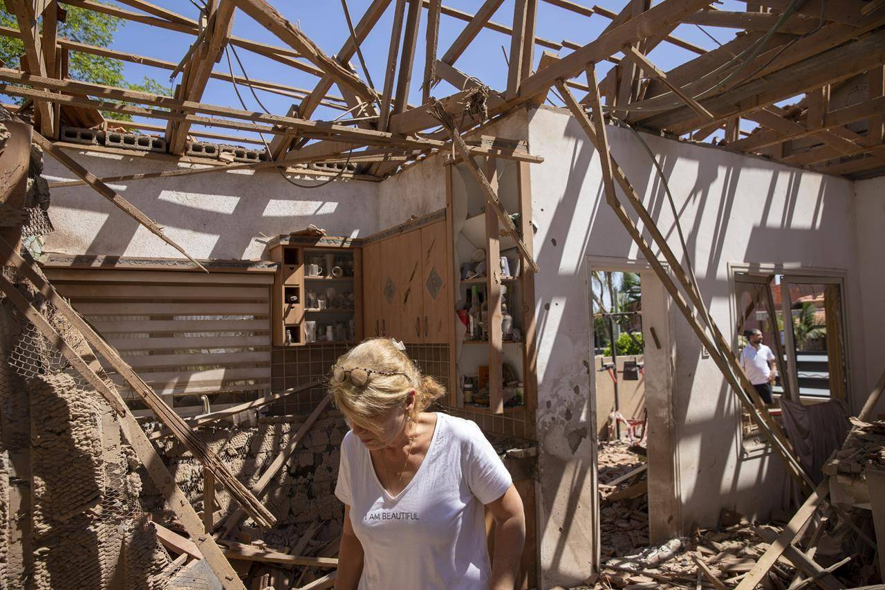 A woman surveys the damage in her home after it was struck by a rocket fired from the Gaza Strip, in Sderot, southern Israel, Saturday, May 15, 2021. (AP Photo/Ariel Schalit),