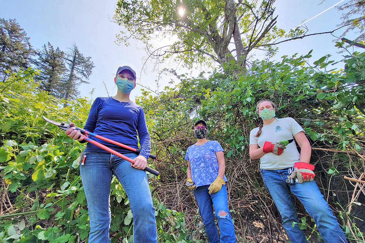 Volunteers Jessica Horst (L) and Angela Womitowy (center) and Lisa Dreves, LEPS Stewardship Coordinator (R) stand in the middle of a clearing they hacked out near Betrand Creek on Saturday, May 15 (Dan Ferguson/Langley Advance Times)