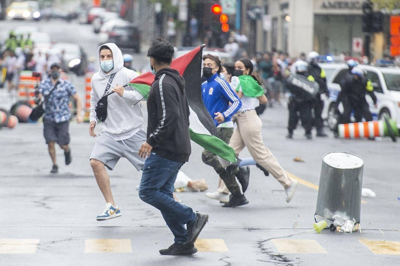 Pro-Palestinian protesters run from police following a demonstration in Montreal, Sunday, May 16, 2021. THE CANADIAN PRESS/Graham Hughes