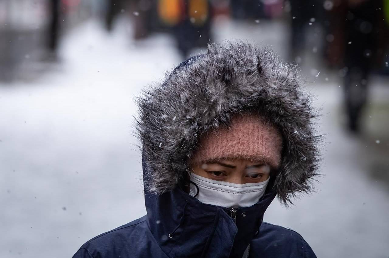 A pedestrian wearing a mask to curb the spread of COVID-19 is bundled up for the cold weather as snow falls in downtown Vancouver on Saturday, February 13, 2021.THE CANADIAN PRESS/Darryl Dyck