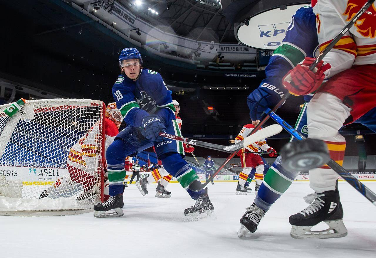 Vancouver Canucks' Jake Virtanen (18) and Calgary Flames' Josh Leivo, front right, vie for the puck as goalie Jacob Markstrom, back left, watches during the first period of an NHL hockey game in Vancouver, on Saturday, February 13, 2021. THE CANADIAN PRESS/Darryl Dyck