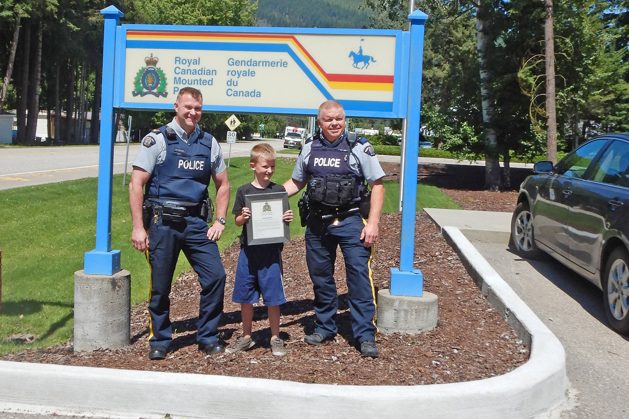 Sicamous RCMP Sgt. Murray McNeil and Cpl. Wade Fisher present seven-year-old Cody Krabbendam of Ranchero with an award for bravery on July 22, 2020. (Contributed)