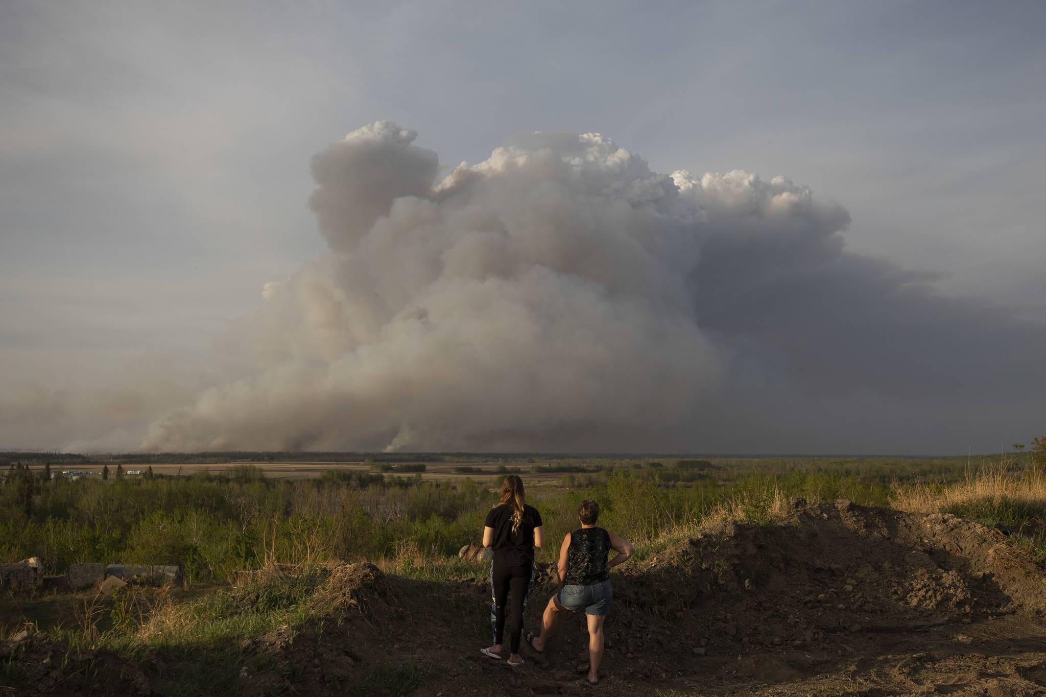 Residents of Prince Albert watch a plume of smoke rise from a forest fire burning northeast of the city in Prince Albert, Sask., Monday, May 17, 2021. The northern Saskatchewan city has declared a local state of emergency due to a wildfire that's fast-moving and forcing some residents to flee for safety. THE CANADIAN PRESS/Kayle Neis