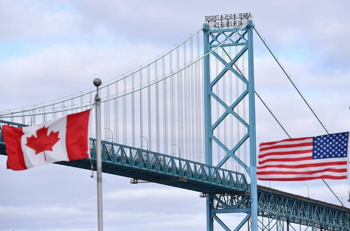 Canadian and American flags fly near the Ambassador Bridge at the Canada-USA border crossing in Windsor, Ont. on Saturday, March 21, 2020. Canadian residents are allowed to head to the United States for a COVID-19 vaccine and avoid quarantine on return if they meet some straightforward conditions, the Public Health Agency of Canada confirms.THE CANADIAN PRESS/Rob Gurdebeke