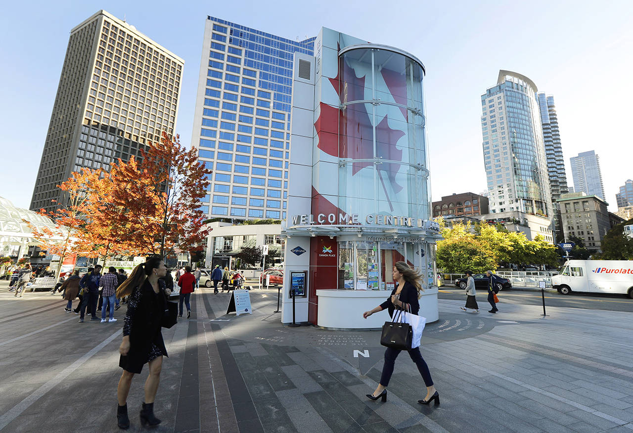 In this Sept. 25, 2018 photo, visitors walk near Canada Place, a tourism and convention center in Vancouver, British Columbia. (AP Photo/Ted S. Warren)