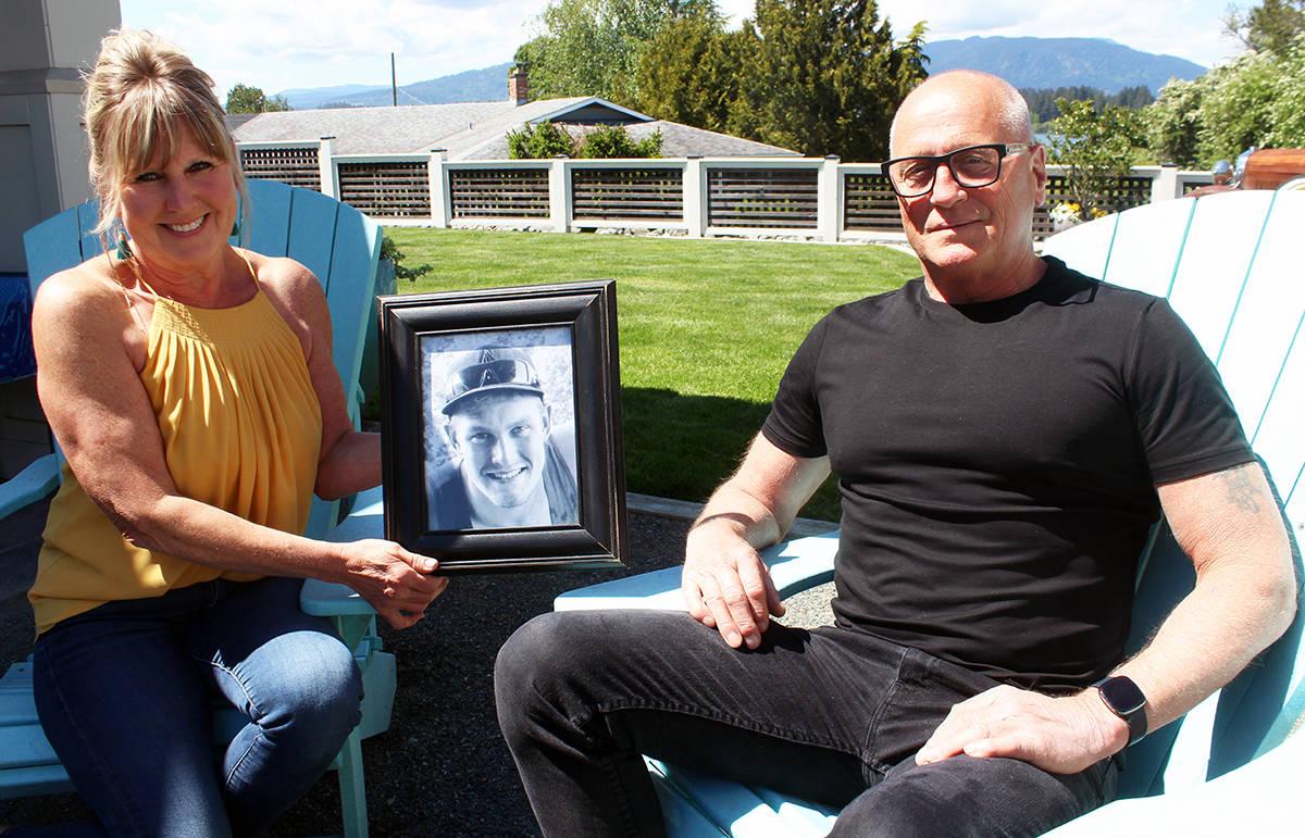 Brenda and Steve Smith with a photo of Derek Descoteau. It's been five years since Derek was murdered in Chemainus. (Photo by Don Bodger)