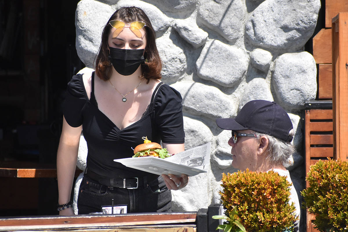A restaurant server on White Rock's Marine Drive serves customers on a roadside patio. Indoor dining and recreational travel bans have been in effect since late March in B.C. (Peace Arch News)