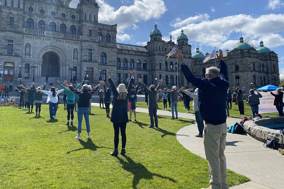 A forest of dance-protesters outside the BC Legislature on April 11. These participants were doing the Dance for the Ancient Forest in support of the Fairy Creek blockade and against old-growth logging. (Zoë Ducklow/News Staff)