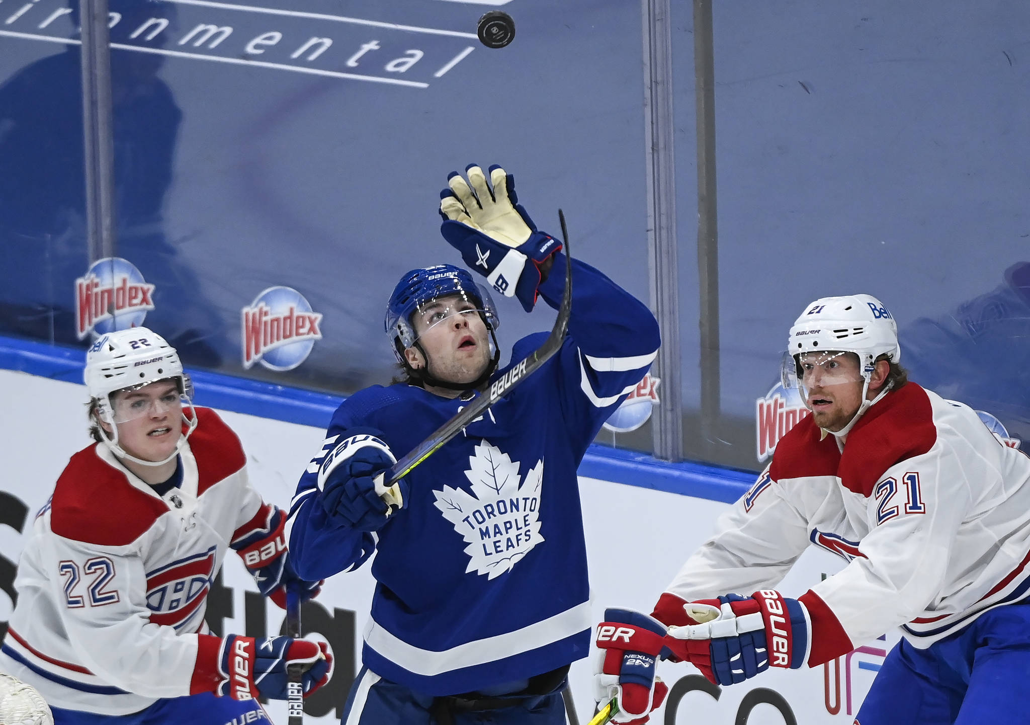 Toronto Maple Leafs defenceman Ben Hutton (55) gloves the loose puck as Montreal Canadiens forward Cole Caufield (22) and Canadiens forward Eric Staal (21) watch during third period NHL hockey action in Toronto on Saturday, May 8, 2021. THE CANADIAN PRESS/Nathan Denette