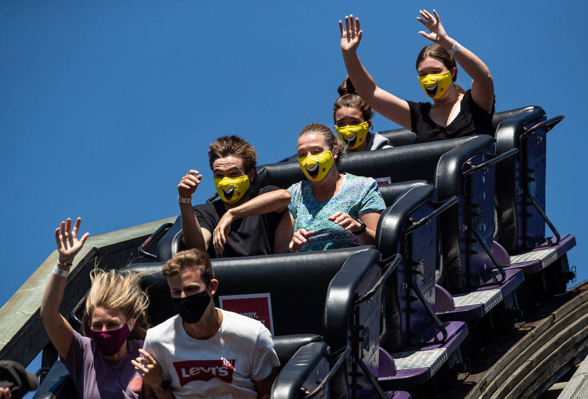 People wear face masks while riding the wooden roller coaster at Playland amusement park at the Pacific National Exhibition. (Darryl Dyck)