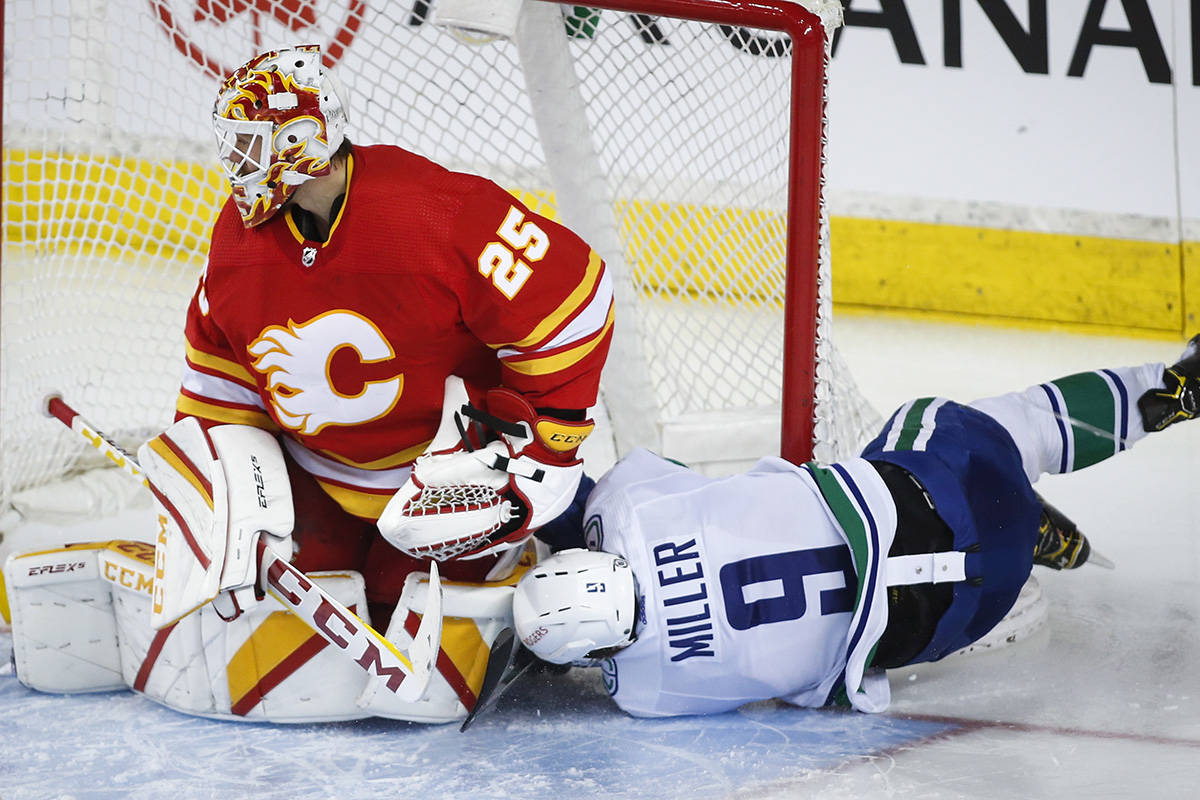 Vancouver Canucks' J.T. Miller, right, crashes into the net after being checked as Calgary Flames goalie Jacob Markstrom follows the play during third period NHL hockey action in Calgary, Wednesday, May 19, 2021.THE CANADIAN PRESS/Jeff McIntosh
