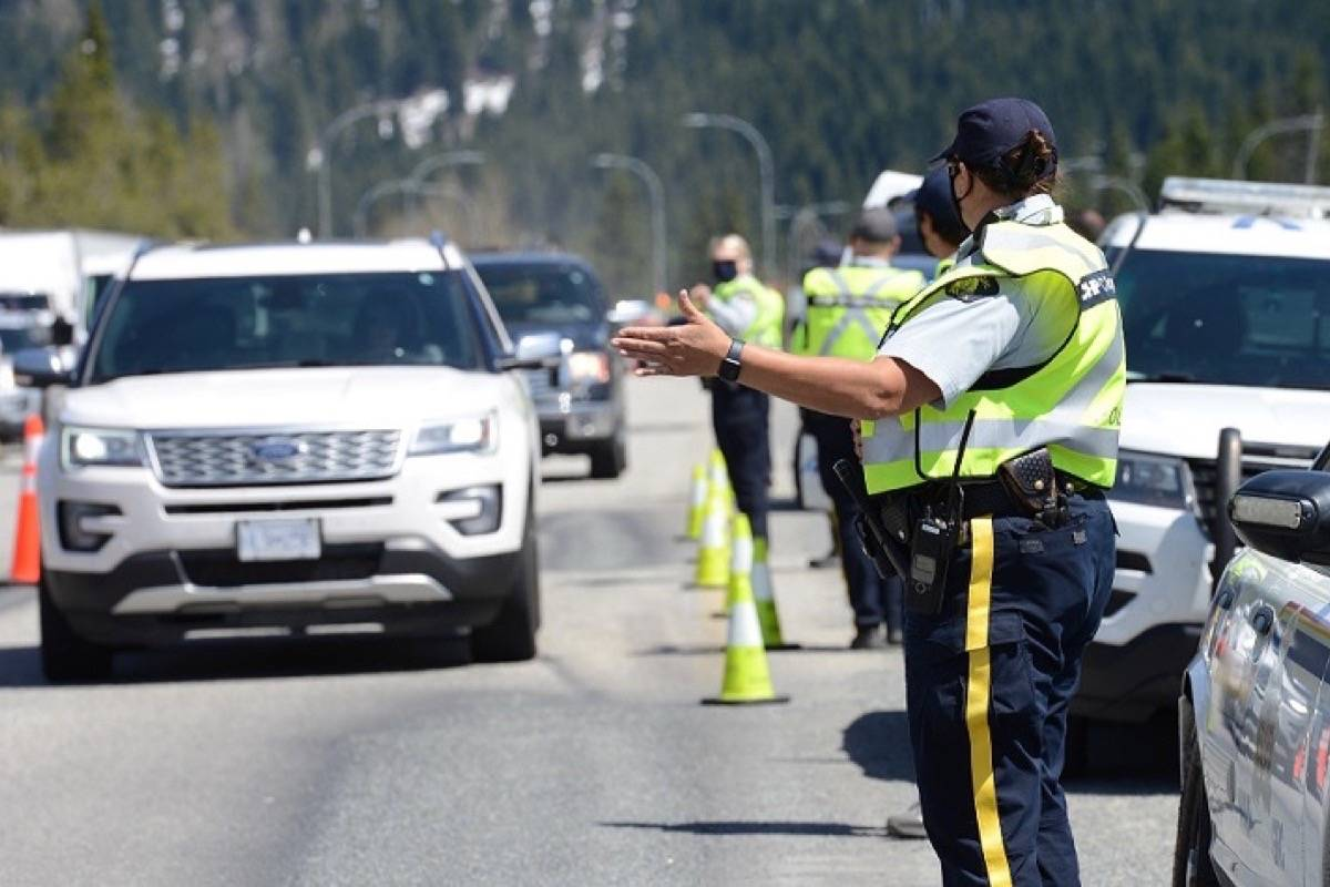 RCMP officers stop vehicles at one of the COVID-19 essential travel stops on highways into B.C.'s Lower Mainland. (B.C. RCMP photo)