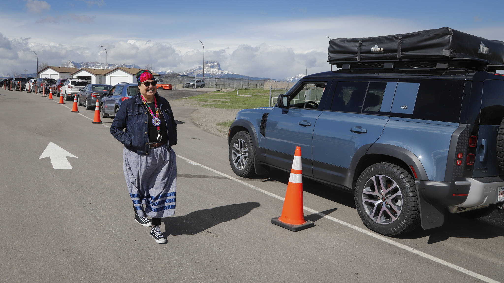 Bonnie Healey, health director for the Blackfoot Confederacy, chats with southern Alberta residents lining up to get shots of a COVID-19 vaccine from a Montana tribe in Carway, Alta., Tuesday, May 18, 2021. THE CANADIAN PRESS/Jeff McIntosh
