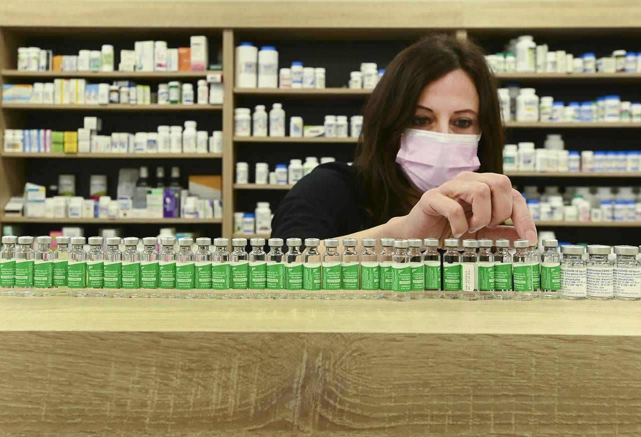 Pharmacist Barbara Violo arranges all the empty vials of the Oxford-AstraZeneca COVID-19 vaccines at the Junction Chemist during the COVID-19 pandemic in Toronto, on Monday, April 19, 2021. THE CANADIAN PRESS/Nathan Denette