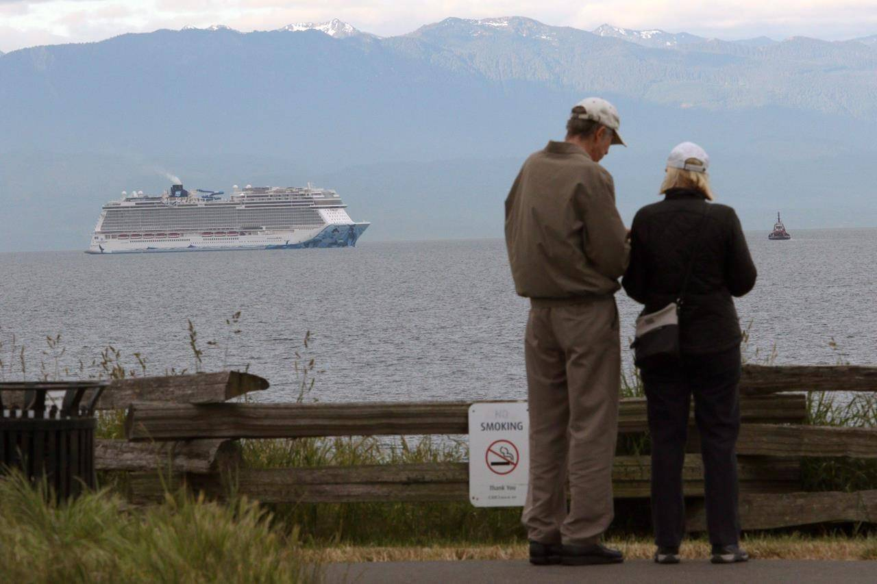 People look on as the Norwegian Bliss en route from Alaska to Seattle makes it's way towards Ogden Point, in Victoria, B.C., Friday, June 1, 2018. The CEO of the Greater Victoria Harbour Authority said he tried to alert Canadian and B.C. politicians to the ramifications of the change that would temporarily allow international cruise ships to bypass B.C. ports. THE CANADIAN PRESS/Chad Hipolito