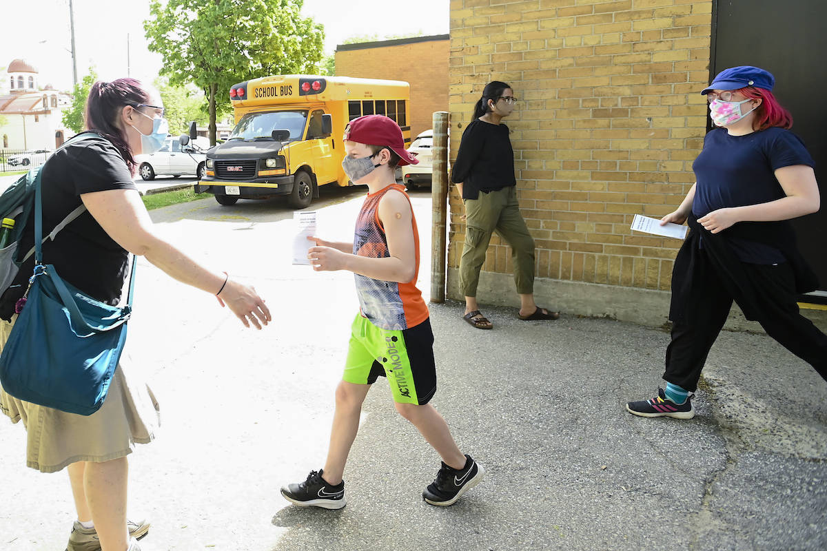 Jessica Lundeen, left, waits to hug her two kids Austin Lundeen, 12, centre, and Chantal Lundeen, 14, after receiving their COVID-19 Vaccine at Gordon A Brown Middle School in Toronto Wednesday, May 19, 2021. THE CANADIAN PRESS/Nathan Denette