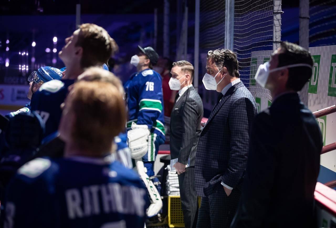 Vancouver Canucks head coach Travis Green, second right, and assistant coaches Newell Brown, back centre, and Nolan Baumgartner, right, stand on the bench before NHL hockey action against the Calgary Flames in Vancouver, B.C., Tuesday, May 18, 2021. The Canucks are giving Green a vote of confidence with a multi-year contract after a tough season on the ice that saw the NHL club sidelined by a COVID-19 outbreak and finish last in the North Division with a 23-29-4 record. THE CANADIAN PRESS/Darryl Dyck