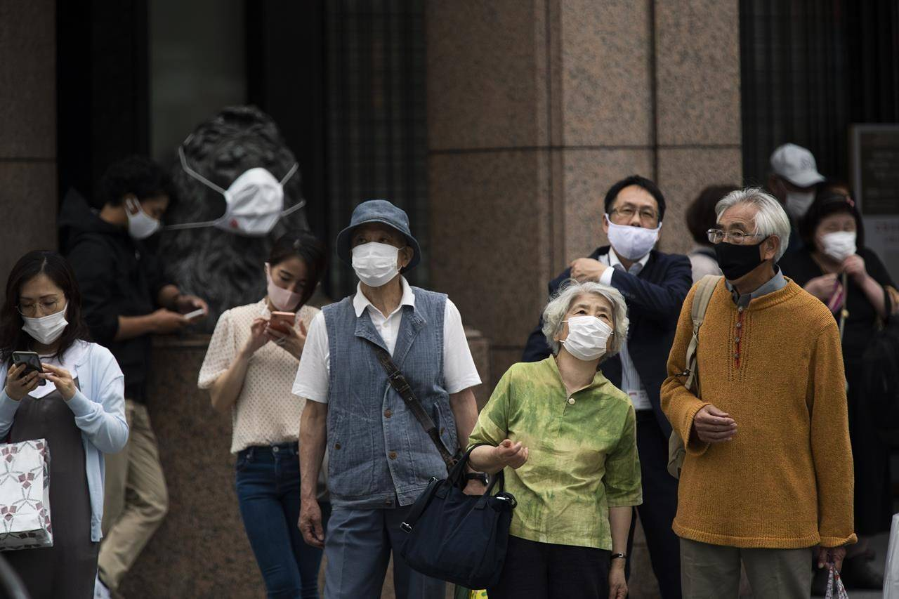 People wearing face masks, wait to walk across a traffic intersection in the famed Ginza shopping neighborhood in Tokyo on Friday, May 21, 2021. Japan has approved the use of two new vaccines - Moderna and AstraZeneca - hours ahead of an expansion of a state of coronavirus emergency that will cover roughly 40% of the population. It's the latest effort to contain a worrying surge in infections nine weeks ahead of the opening of the Tokyo Olympics.(AP Photo/Hiro Komae)