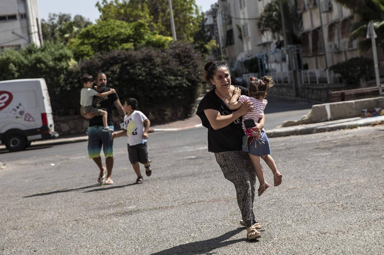 Lia Tal, 40, rushes with her children and partner to take shelter as a siren sounds a warning of incoming rockets fired from the Gaza Strip, In Ashdod, Israel, Thursday, May 20, 2021. (AP Photo/Heidi Levine)