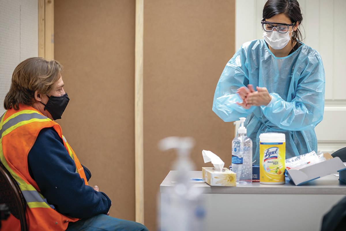 A health care worker prepares to test a Coastal GasLink field worker for COVID-19. (Coastal GasLink photo)