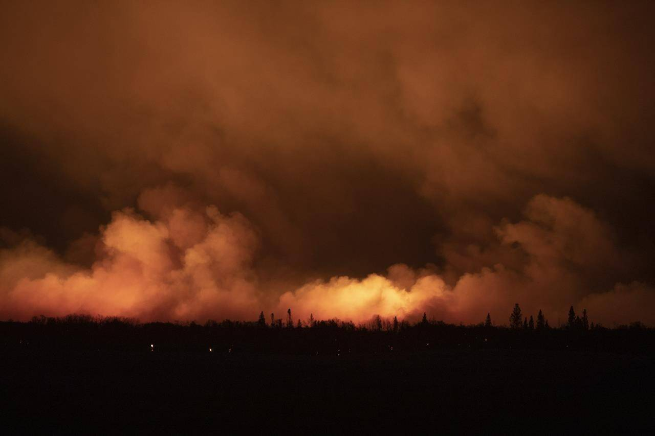 A forest fire burns late into the evening northeast of Prince Albert, Sask., on Monday, May 17, 2021. THE CANADIAN PRESS/Kayle Neis