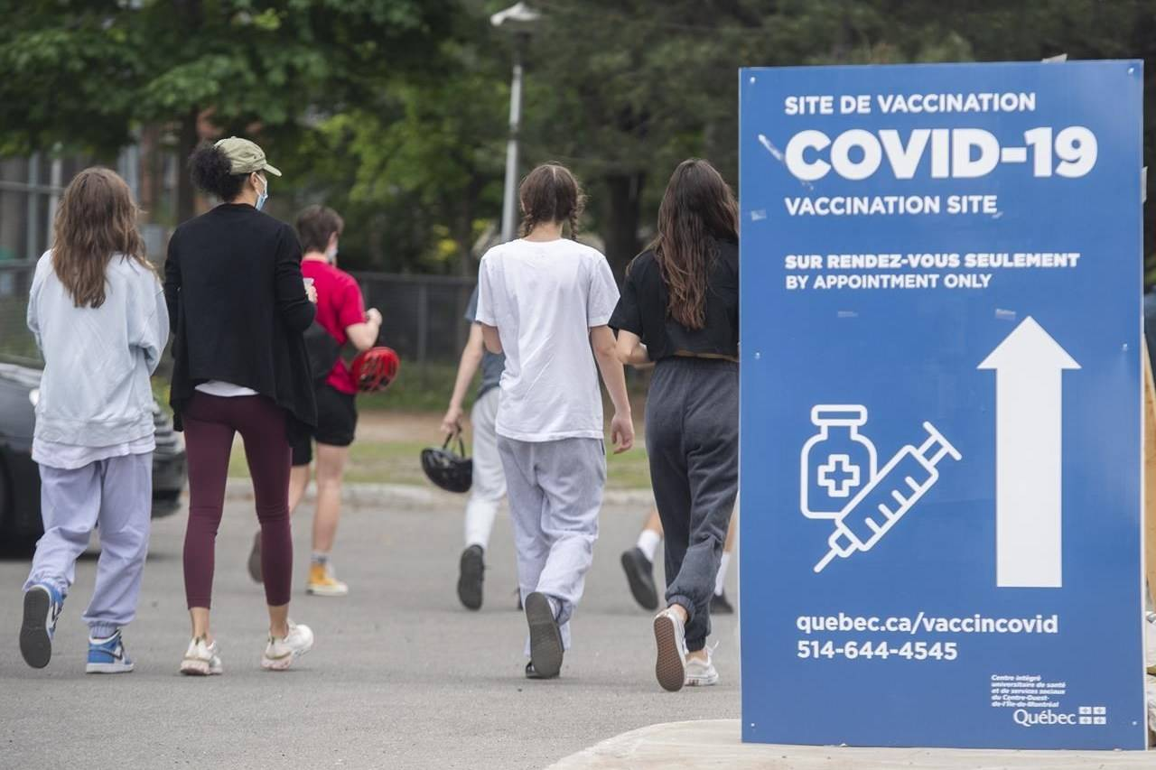 Young people walk into a COVID-19 vaccination site in Montreal, Saturday, May 22, 2021. More than 50 per cent of Canadians have now received at least one dose of vaccine. THE CANADIAN PRESS/Graham Hughes