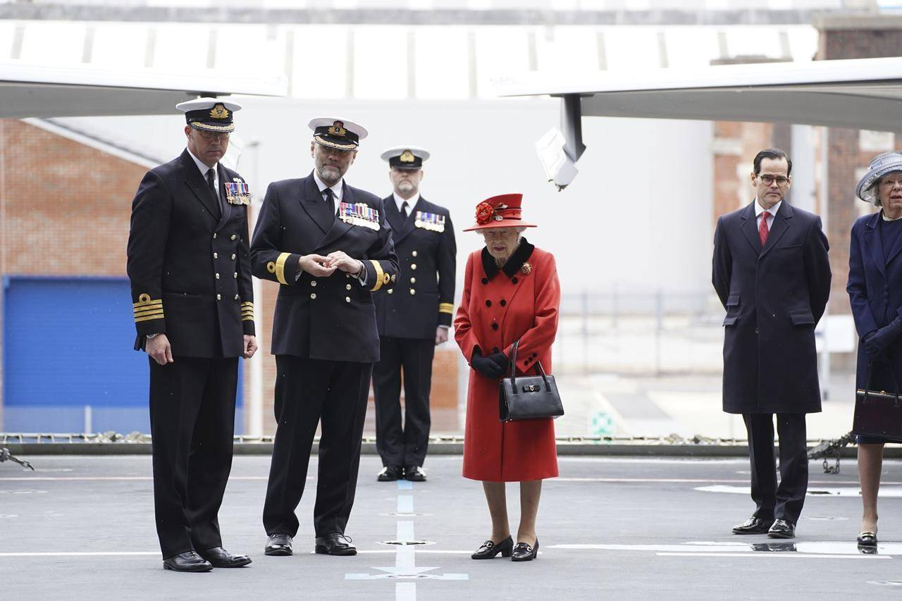 Captain Angus Essenhigh , left, , Commodore Steve Moorhouse, second from left, accompany Britain's Queen Elizabeth II , centre, on the flight deck, during a visit to HMS Queen Elizabeth at HM Naval Base, ahead of the ship's maiden deployment, in Portsmouth, England, Saturday May 22, 2021. HMS Queen Elizabeth will be leading a 28-week deployment to the Far East that Prime Minister Boris Johnson has insisted is not confrontational towards China. (Steve Parsons/Pool Photo via AP)