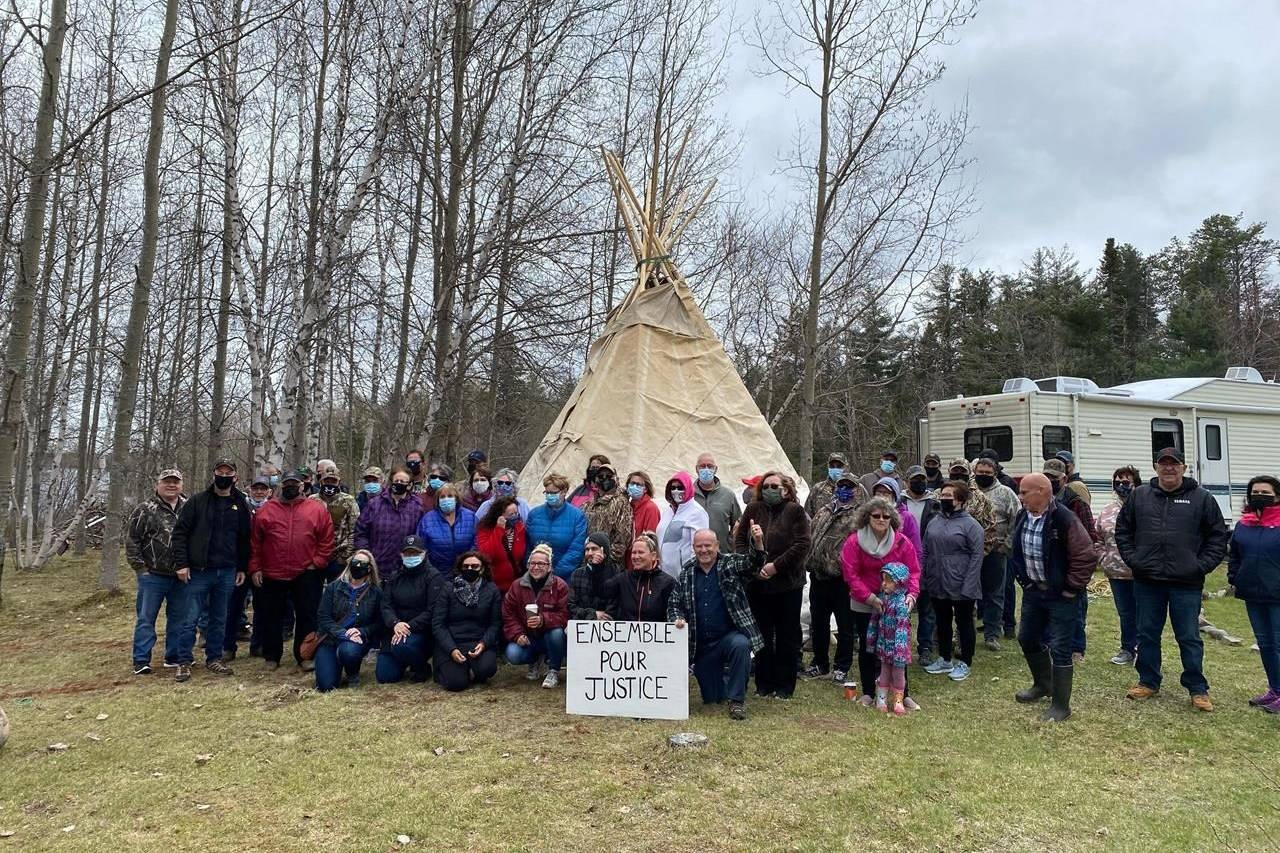 """Some members of the 67 families who continue the fight with Parks Canada over expropriation are shown in Kouchibouguac National Park in New Brunswick on Wednesday, May 19, 2021. Their sign in French reads, """"Together for Justice."""" THE CANADIAN PRESS/Kevin Bissett"""
