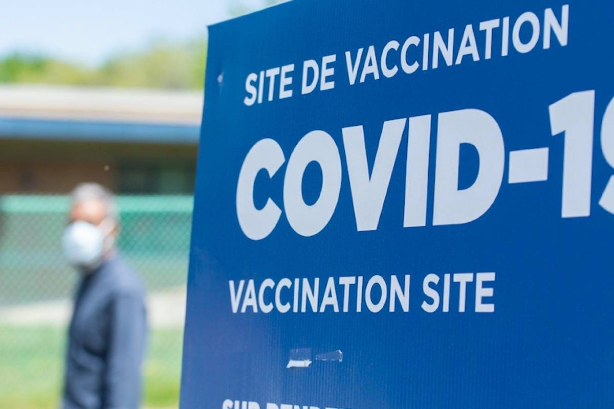 A man wears a face mask as he walks by a sign for a COVID-19 vaccination site in Montreal, Sunday, May 16, 2021, as the COVID-19 pandemic continues in Canada and around the world. THE CANADIAN PRESS/Graham Hughes