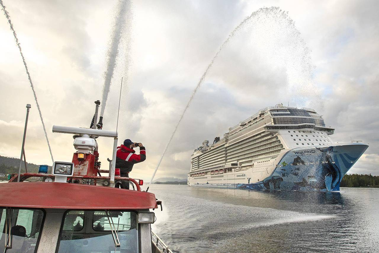 Firefighter medic Andy Tighe snaps a photo of the breakaway plus-class cruise ship Norwegian Bliss while Captain Tracy Mettler operates a fireboat in the Tongass Narrows in Ketchikan, Alaska, on June 4, 2018. President Joe Biden signed into law Monday, May 24, 2021, legislation that opens a door for resumed cruise ship travel to Alaska after the pandemic last year scrapped sailings. (Dustin Safranek/Ketchikan Daily News via AP)