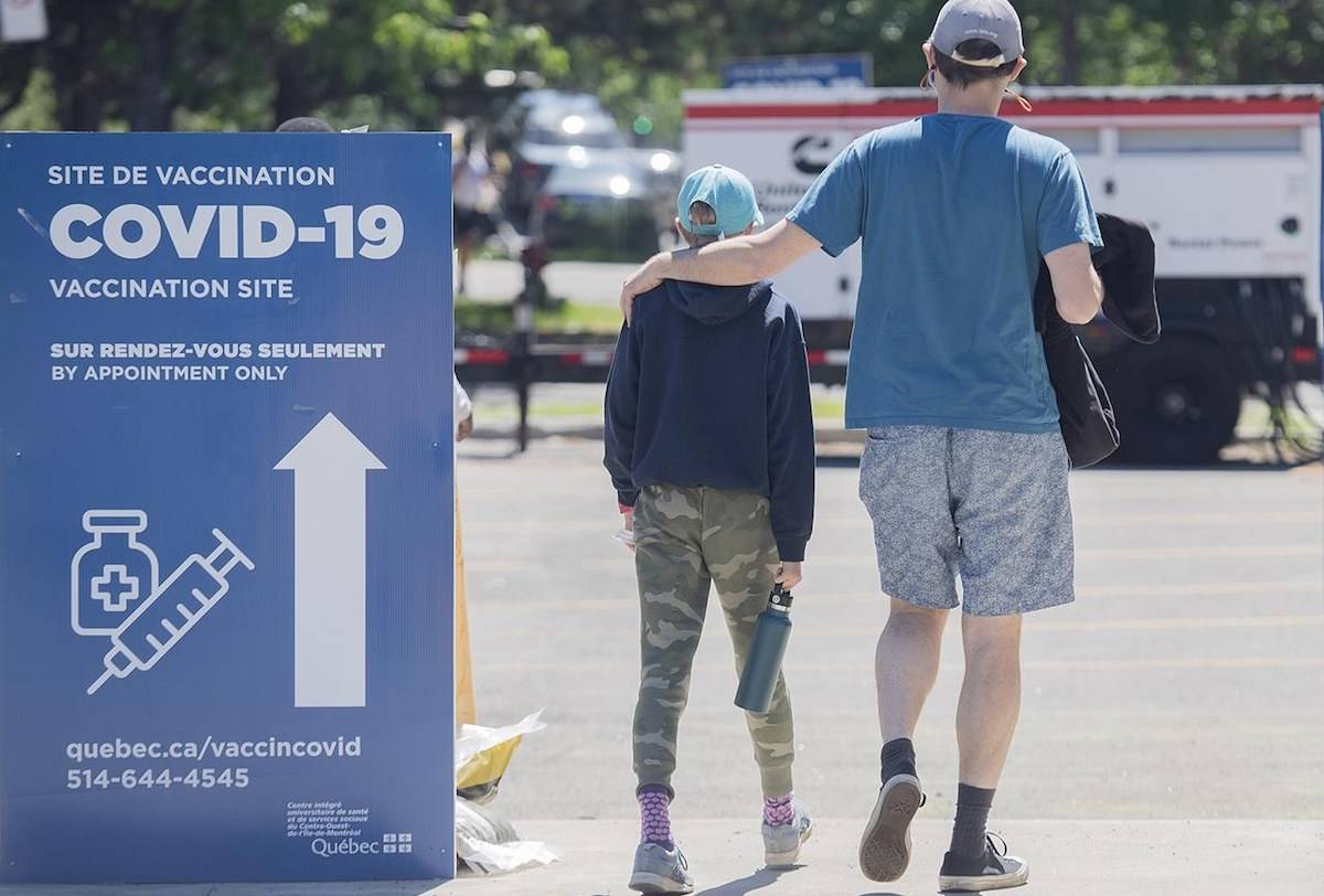 A man and boy walk into the Bill-Durnan COVID-19 vaccination site in Montreal, Monday, May 24, 2021. THE CANADIAN PRESS/Graham Hughes