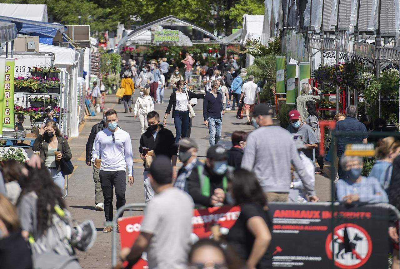 People wear face masks as they walk through the Atwater Market in Montreal, Monday, May 24, 2021, as the COVID-19 pandemic continues in Canada and around the world. THE CANADIAN PRESS/Graham Hughes