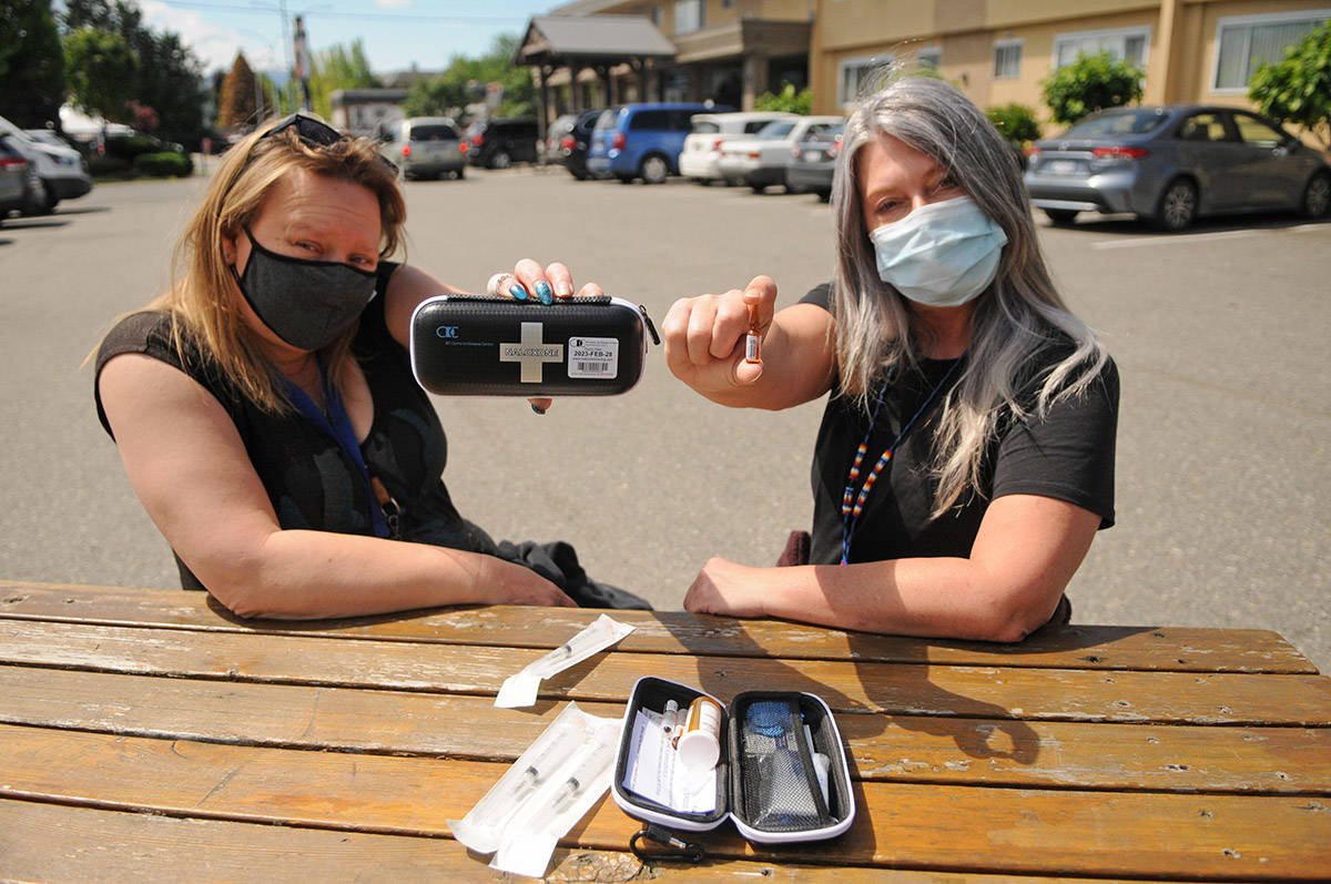 Jodi Higgs (right) holds a vial of naloxone and Christine Christensen holds a kit in the parking lot of the Pacific Community Resources Society in Chilliwack on Thursday, May 20, 2021. The society is offering a number of upcoming events, workshops and videos to help educate friends and family members who have loved ones that are drug users. (Jenna Hauck/ Chilliwack Progress)