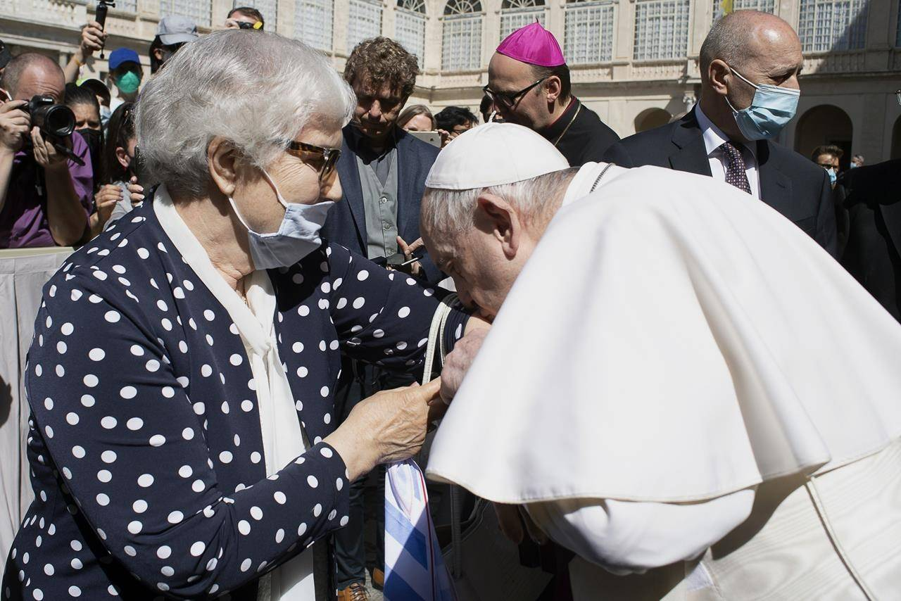 Pope Francis leans and kiss a tattoo on the arm of Holocaust survivor Lidia Maksymowicz, a Polish citizen who was deported to Auschwitz from her native Belarus. (Vatican Media via AP)