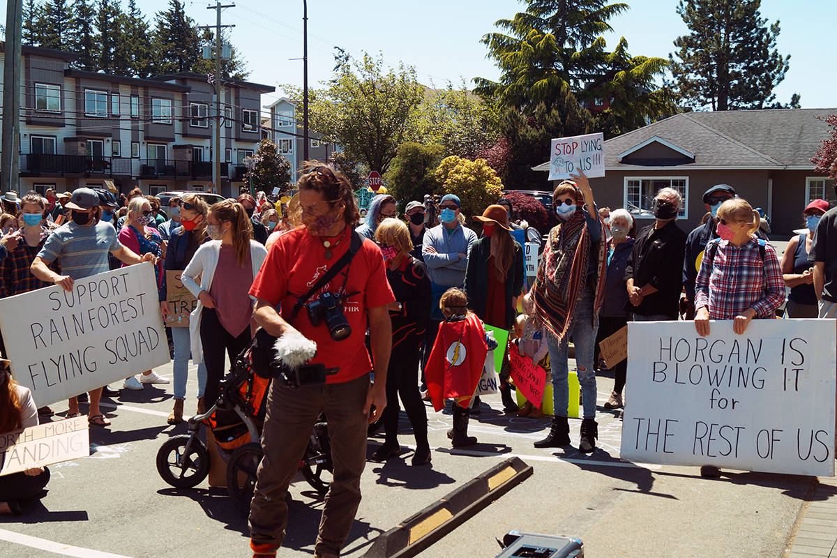Protesters gather outside Premier John Horgan's constituency office in Langford on Friday to protest the logging of old-growth forests. (Rick Stiebel/News Staff)
