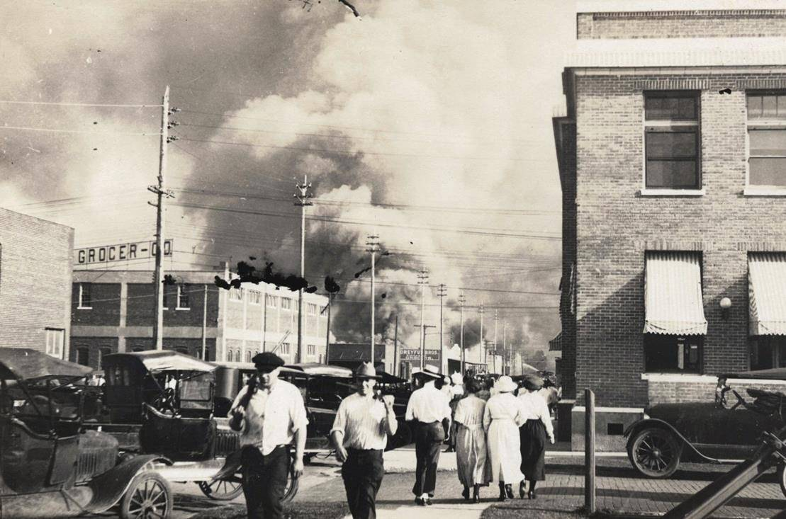 FILE - In this photo provided by Department of Special Collections, McFarlin Library, The University of Tulsa, two armed men walk away from burning buildings as others walk in the opposite direction during the June 1, 1921, Tulsa Race Massacre in Tulsa, Okla. (Department of Special Collections, McFarlin Library, The University of Tulsa via AP, File)