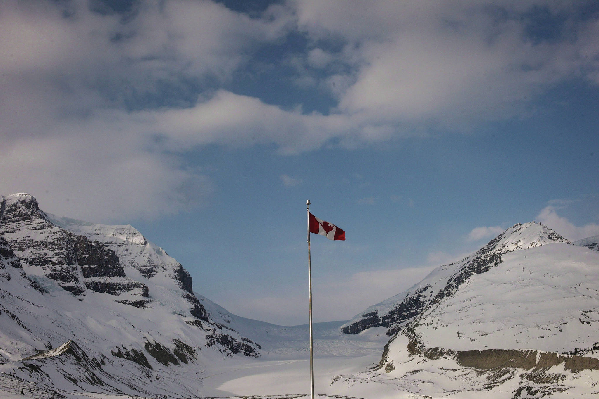 FILE – The Canadian flag flies over the Columbia Icefields' Athabasca Glacier in Jasper National Park, on May 7, 2014. THE CANADIAN PRESS/Jeff McIntosh, File