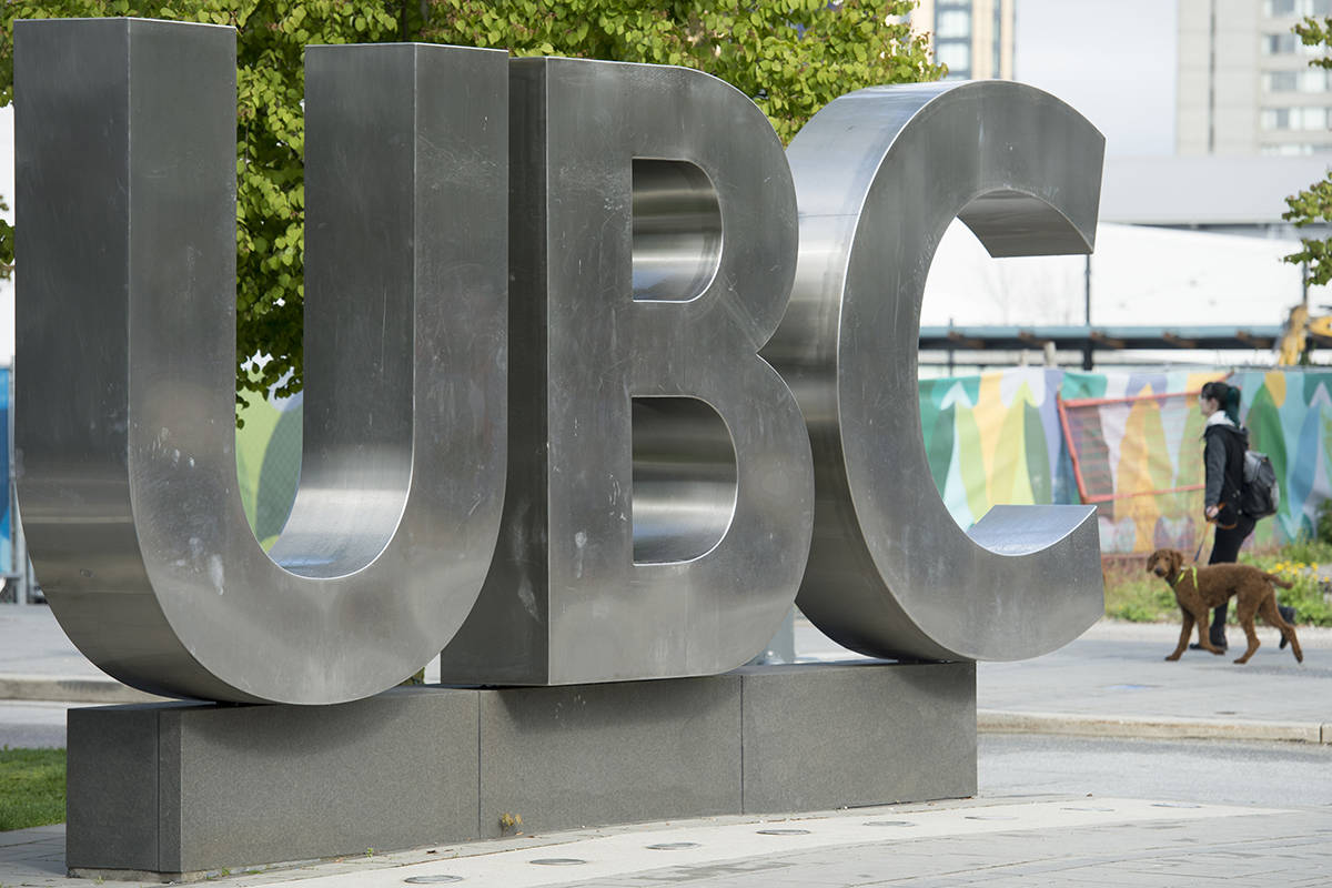FILE – A woman and her dog walks past the UBC sign at the University of British Columbia in Vancouver, Tuesday, Apr 23, 2019. THE CANADIAN PRESS/Jonathan Hayward