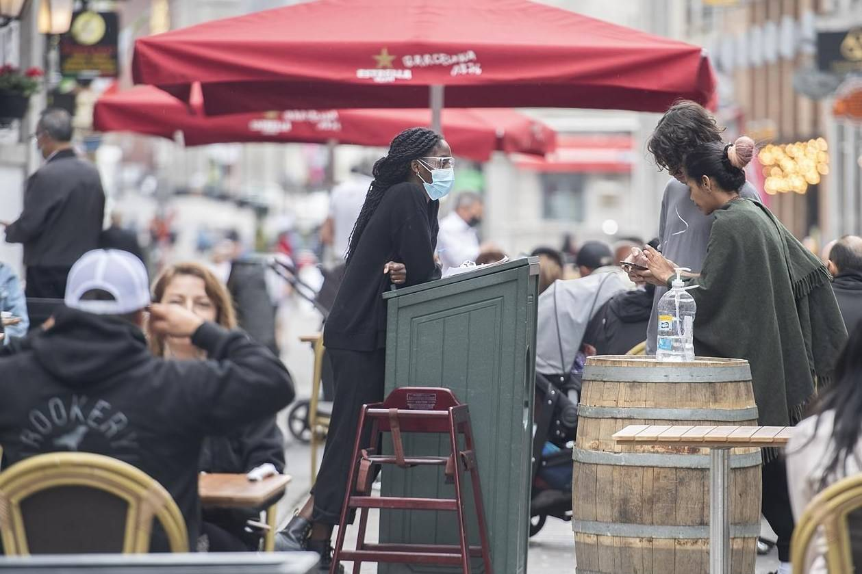 A greeter wears a face mask as people wait for a table at a restaurant in Old Montreal, Sunday, May 30, 2021. THE CANADIAN PRESS/Graham Hughes