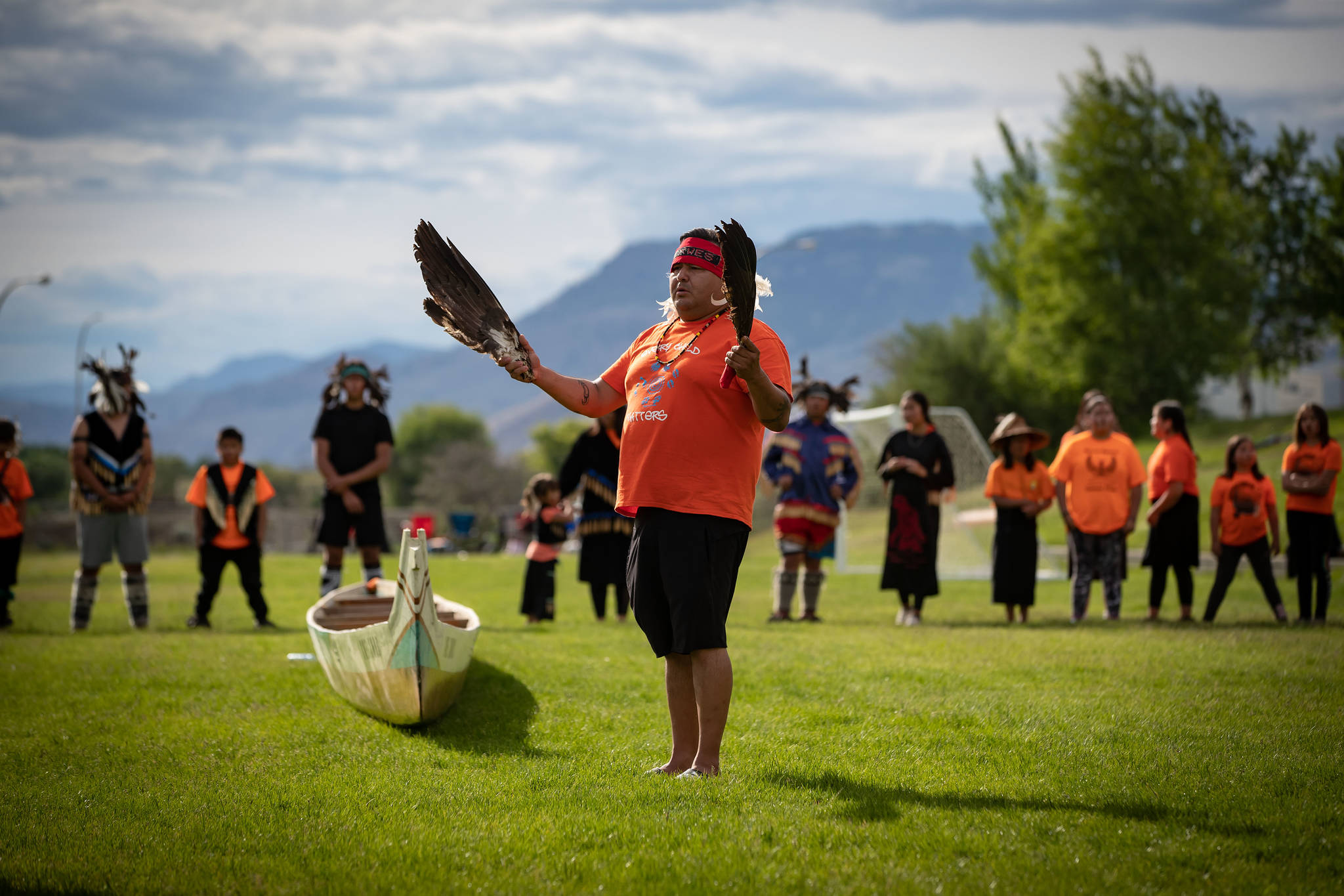 Jonny Williams (Xotxwes), of the Sto:lo Nation, holds eagle feathers as he helps guide his late ancestors from an unmarked, undocumented burial site to a canoe so they can travel home, outside the former Kamloops Indian Residential School, in Kamloops, B.C., on Monday, May 31, 2021. The remains of 215 children have been discovered buried near the former school. THE CANADIAN PRESS/Darryl Dyck