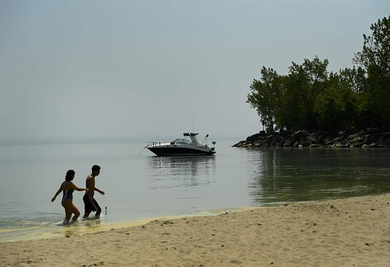 People walk in Lake Ontario on a warm sunny day at Woodbine Beach during the COVID-19 pandemic in Toronto on Tuesday, May 25, 2021. THE CANADIAN PRESS/Nathan Denette