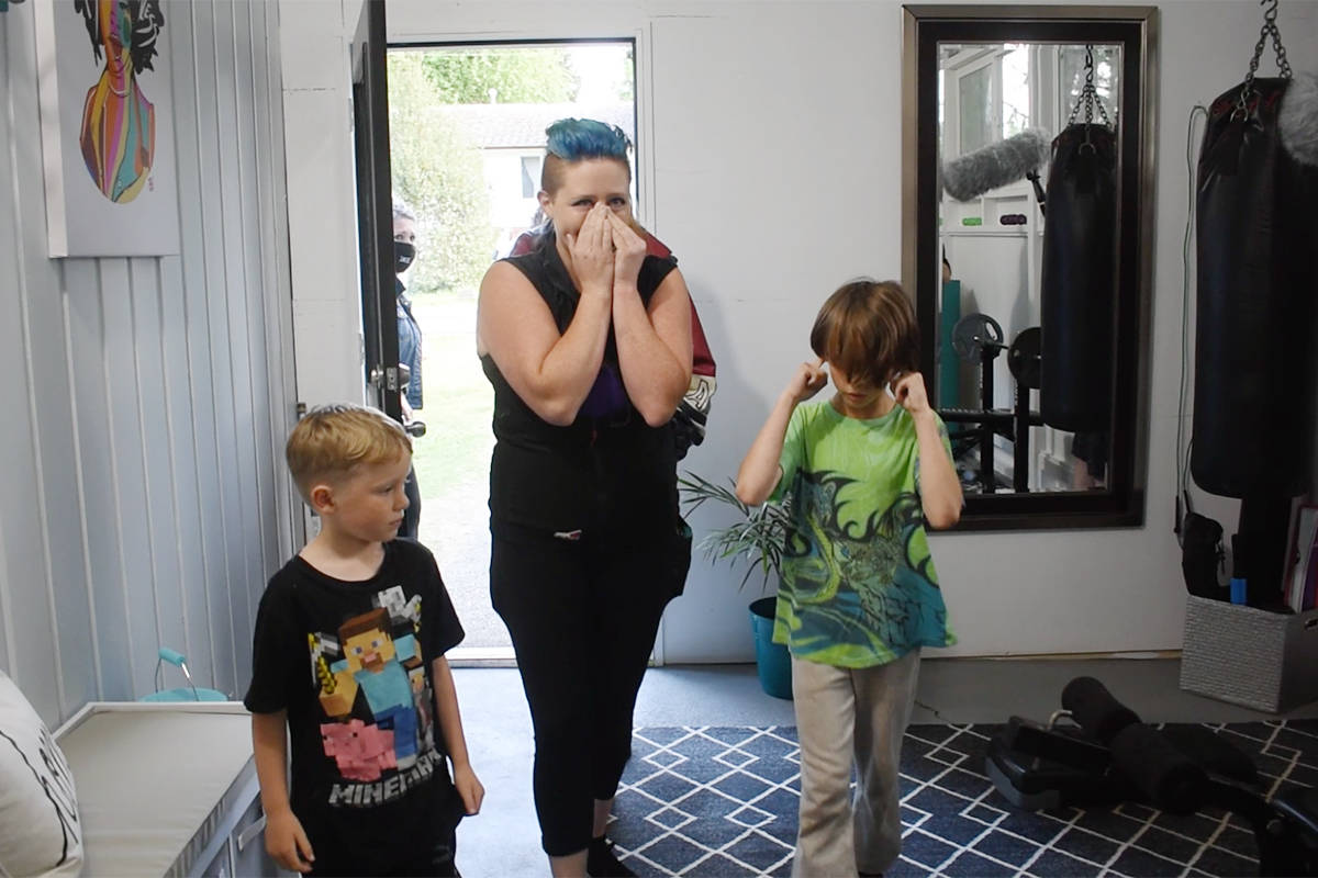 Rachelle Seidel walks into her newly renovated home for the first time with her children Sunday evening. (Aaron Hinks photo)