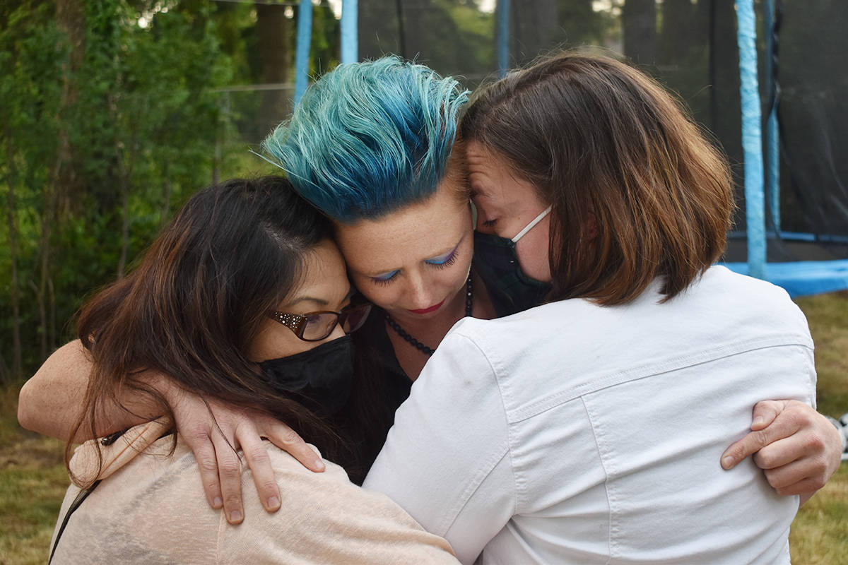 Rachelle Seidel receives a hug from her two friends Grace Ma (left), and Naomi Kragh. (Aaron Hinks photo)