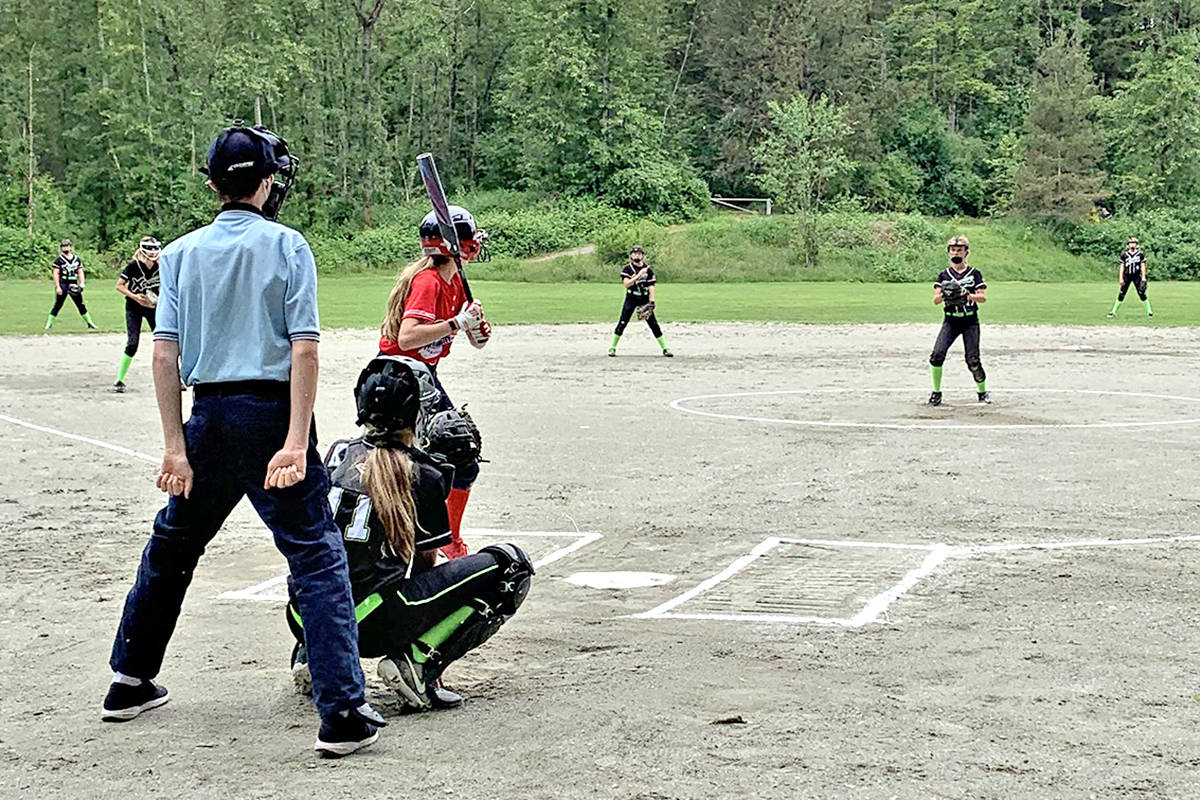 Batter Rachel Clegg faced pitcher Makenna Adler-Bock with catcher Ashlen Kenna and umpire Mason Clegg on Sunday, May 30. Fraser Valley Fusion 10A (in red) was playing against Langley Xtreme 09B as the Langley Fastball Association resumed play following a provincial announcement easing COVID-19 restrictions. (Special to Langley Advance Times)