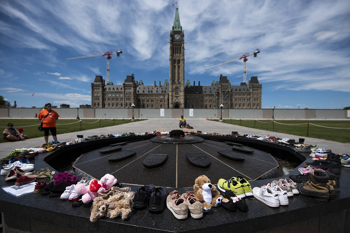 Shoes line the edge of the Centennial Flame on Parliament Hill in memory of the 215 children whose remains were found at the grounds of the former Kamloops Indian Residential School at Tk'emlups te Secwépemc First Nation in Kamloops, B.C., on Sunday, May 30, 2021, THE CANADIAN PRESS/Justin Tang