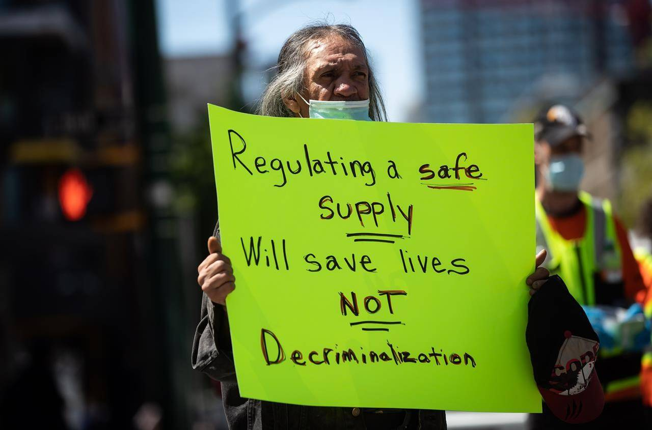 A man holds a sign during a protest against the proposed Vancouver Model for illicit drug decriminalization, in the Downtown Eastside of Vancouver, on May 11, 2021. THE CANADIAN PRESS/Darryl Dyck