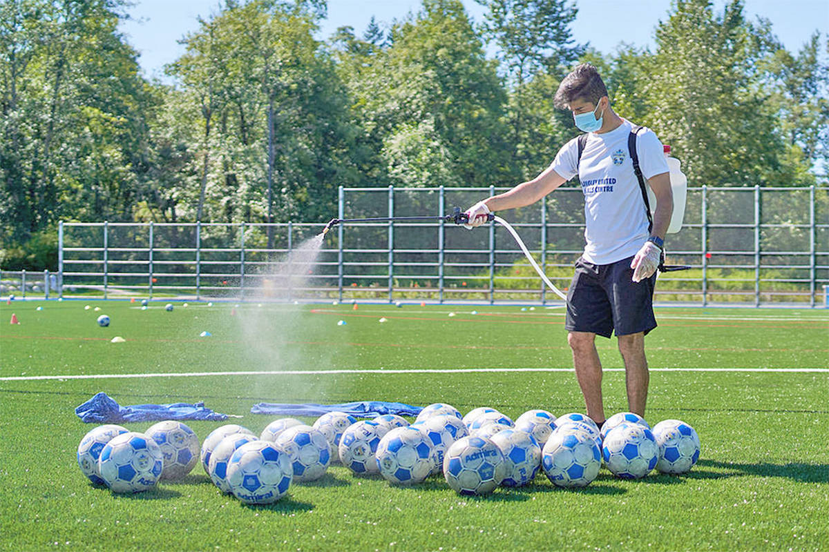 Soccer balls got a COVID-19 precautionary cleaning by Azad Palani at a Langley United Soccer Association training session at Willoughby park in July 2020. (file)