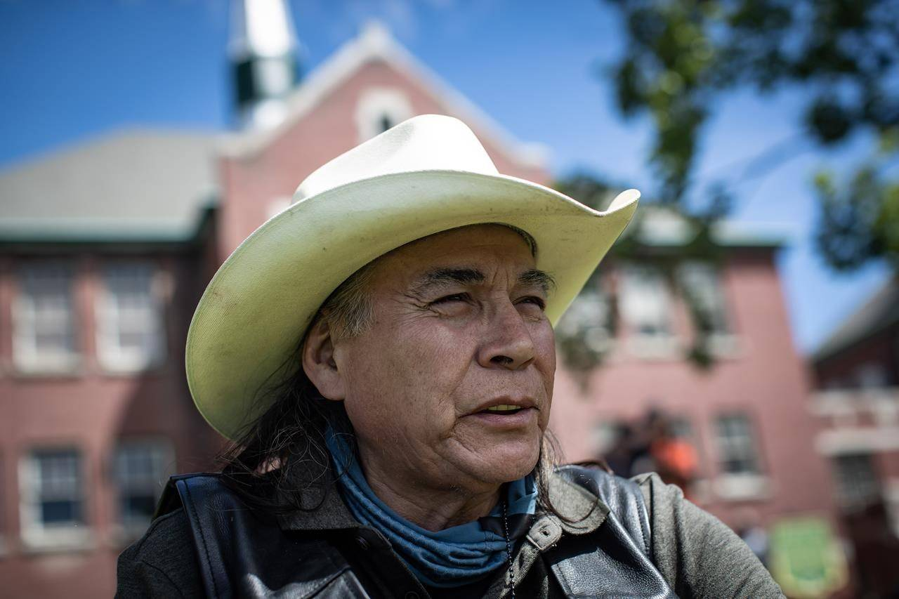 Kamloops Indian Residential School survivor Clayton Peters, 64, who was forced into the school for 10 years, sits on the lawn at the former school, in Kamloops, B.C., on Monday, May 31, 2021. Peters' parents and his brothers were also forced into the facility. The remains of 215 children have been discovered buried near the former school. THE CANADIAN PRESS/Darryl Dyck